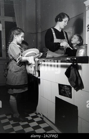 Mitglieder einer kinderreichen Familie bei der Hausarbeit, Deutsches Reich 1930er Jahre. Members of an extended family doing the housework, Germany 1930s. - Stock Photo
