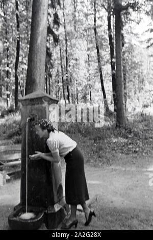 Eine junge Frau probiert das Trinkwasser des Eberbrunnens auf einem Wanderpfad bei Baden-Baden im Nordschwarzwald, Deutschland 1930er Jahre. A young w - Stock Photo