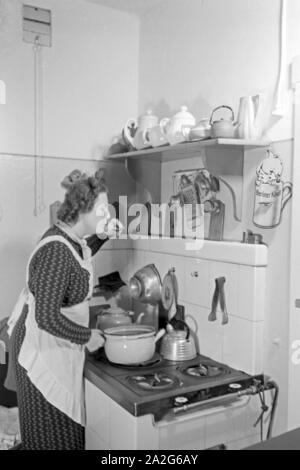Eine Frau steht am Herd in der Küche und kocht, Deutschland 1930er Jahre. A woman standing in the kitchen on the oven cooking, Germany 1930s. - Stock Photo