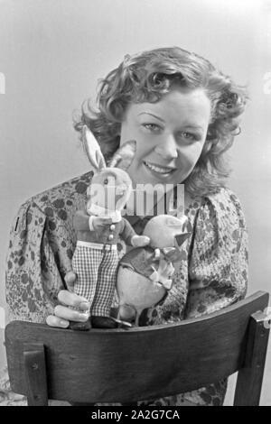 Porträt eines jungen Mädchens, Osterdekoration in den Händen haltend, Deutschland 1930er Jahre. Portrait of a young girl holding some easter decoration in her hands, Germany 1930s. - Stock Photo