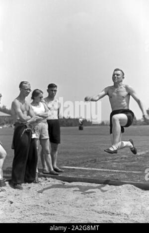 Übung im Weitsprung auf dem Sportplatz des KdF Sportheim Belzig in der Mark Brandenburg, Deutschland 1930er Jahre. Long jump exercising at the sports ground of the sports club house at Belzig in Brandenburg, Germany 1930s. - Stock Photo
