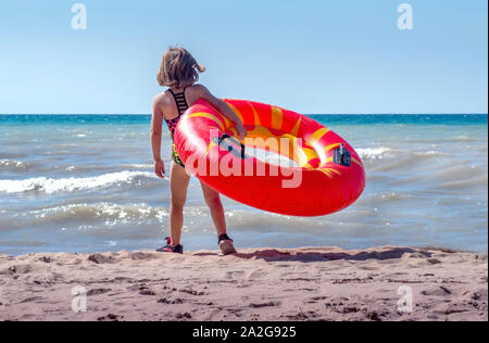 A little girl stands with her flotation ring, trying to decide if she is brave enough to go into Lake Michigan for the first time - Stock Photo