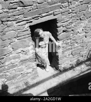 Eine junge Frau schaut aus einer Maueröffnung, Österreich 1930er Jahre. A young woman gazing out of a wall door, Austria 1930s- - Stock Photo
