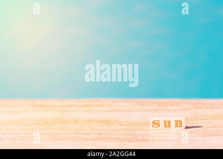 Word sun written by cubes near the pool. Azure water in sunny day used as a background. Sun light and copy space. Summer and vacation concept. - Stock Photo