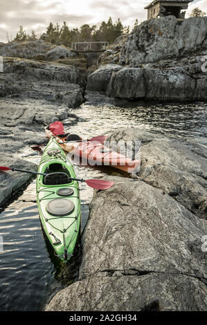 Two kayaks are moored on the rocky shore, in the background you can see the old wooden bridge and hut against a background of cloudy sky and forest. - Stock Photo