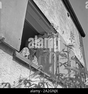 Eine junge Frau schaut aus dem Fenster eines Hauses in ihren Garten, Deutschland 1930er Jahre. A young woman looking out of the window to her garden, Germany 1930s. - Stock Photo