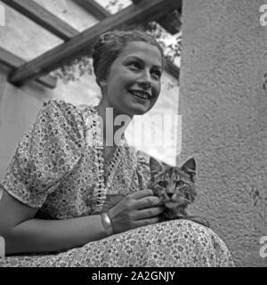 Eine junge Frau sitzt mit einer Katze auf einer Terrasse, Deutschland 1930er Jahre. A young woman and a cat sitting on a terrace, Germany 1930s. - Stock Photo