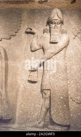 Face-forward Assyrian bearded statue following a human-headed sacred winged bull, Room 10 British Museum. Left facing. One of a pair. Khorsabad. - Stock Photo