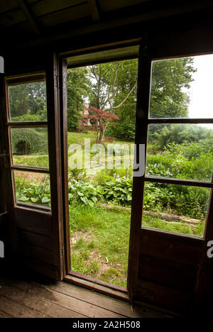 View of a lush garden through the doors and windows of a wooden summer house - Stock Photo