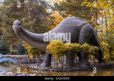 A large gray adult brachiosaurus looks towards the frame and stands on the stone bank of the river, next to small trees and shrubs on a warm autumn da - Stock Photo