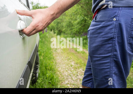 The man opens the door of the car with his hand, which stands on the forest road. Close-up. - Stock Photo