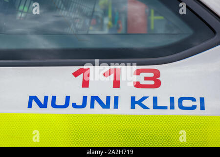 Slovenska Bistrica, Slovenia - Sept 14 2019: Police sign with emergency dial number on the side of patrol car, Slovenia Police Force - Stock Photo