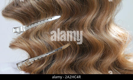 Silver hairdressers clips in wavy hair - close up - Stock Photo