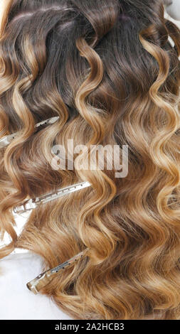 Silver hairdressers clips in curly hair - Stock Photo