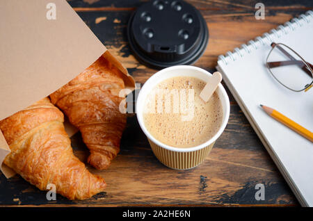 Take away coffee cup with croissant on wooden table. - Stock Photo