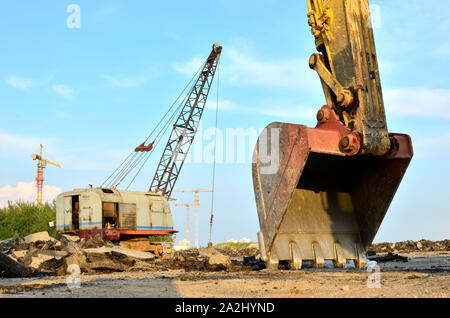 Excavator bucket on the construction site at sunset background and of the blue sky. Land Clearing, grading, pool excavation, utility trenching, utilit - Stock Photo