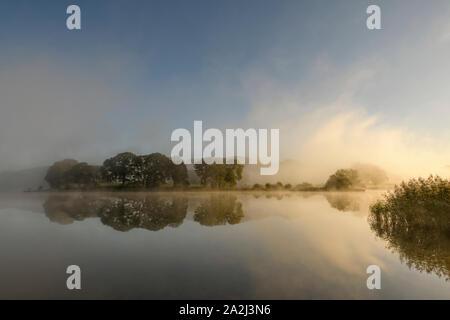 Trees reflected in Esthwaite Water near Hawkshead as the sunshine breaks through the early morning autumn mist