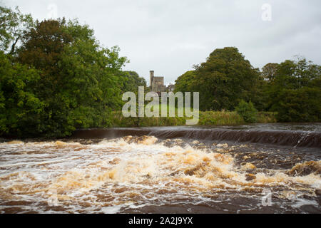 The River Wenning flowing over a weir after heavy rain in Sepember at Hornby village with Hornby Castle in the background. Not far downstream the Wenn - Stock Photo