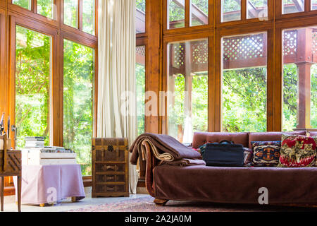 Open plan living place room with old sofa, rustic chest and large french windows looking out to green trees in garden, Lőverek, Sopron, Hungary - Stock Photo