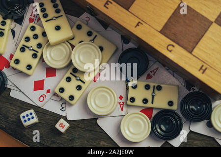 Close up Various board games chess board, playing cards, dominoes on a old wooden table background. - Stock Photo