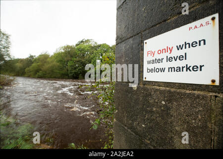 The River Wenning after heavy rain in Sepember at Hornby village. Not far downstream the Wenning joins the river Lune. A fishing club sign indicates t - Stock Photo