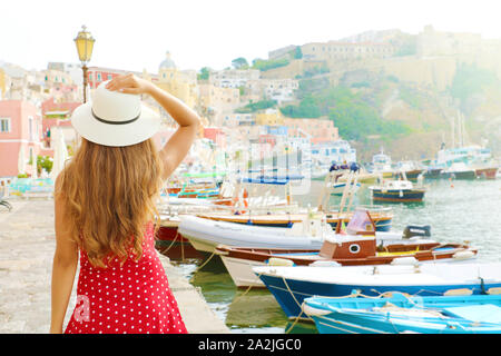 Holidays in Italy. Back view of beautiful girl in stunning colorful harbor of Procida in Italy. Stock Photo