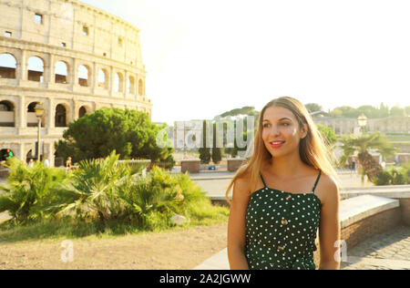 Portrait of smiling beautiful girl in Rome with Colosseum on the background at sunset. Summer holidays in Italy. - Stock Photo
