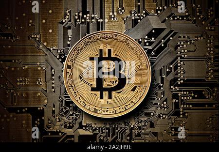 Bitcoin golden coin on computer circuit board - Stock Photo