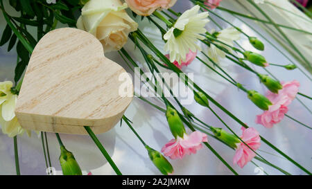 Closed small wooden casket in the shape of a heart and flowers on a white glass background