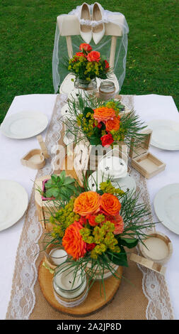 Vintage table decoration with wooden details and orange roses - on a wooden chair bride's white shoes and her veil - Stock Photo