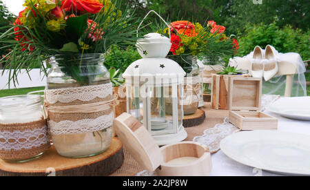 Vintage table decoration with wooden details and orange roses - Stock Photo