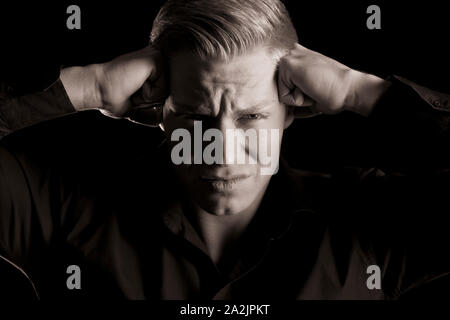 Low key portrait of overburdened young man, black and white. - Stock Photo