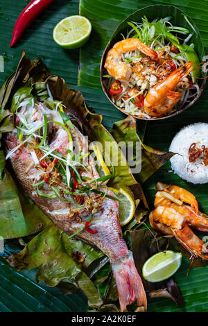 Red snapper baked in banana leaf, papaya salad and rice - Stock Photo