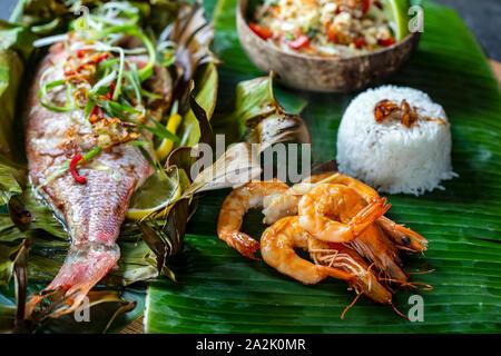 Red snapper baked in banana leaf, papaya salad, prawns and rice - Stock Photo
