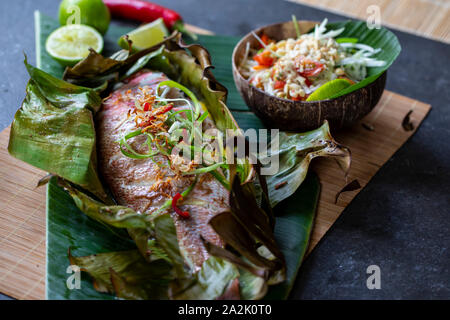 Red snapper baked in banana leaf and papaya salad - Stock Photo