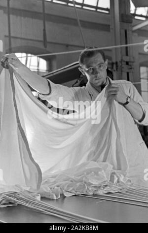 Anpassung des Gurtzeugs eines Fallschirms in einer Fallschirm Näherei, Deutschland 1940er Jahre. Checking the harness of a parachute at a parachute sewing factory, Germany 1940s. - Stock Photo