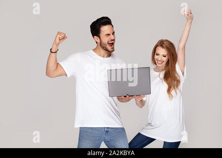 Happy young couple, caucasian guy and girl , using laptop. Studio shot. Copy space. - Stock Photo
