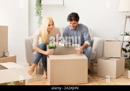 Young man and woman packing things in moving boxes indoor - Stock Photo