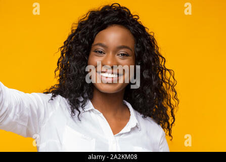 Young black woman holding cellphone and making selfie - Stock Photo