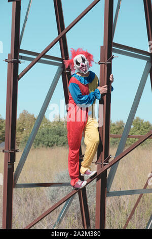 a scary clown, wearing a colorful yellow, red and blue costume outdoors, sticking out his tongue while hanging from the rusty structure of an abandone - Stock Photo