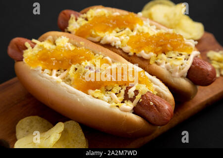 Homemade colombian hot dogs with pineapple sauce, chips and mayo ketchup on a rustic wooden board on a black surface, side view. Closeup. - Stock Photo
