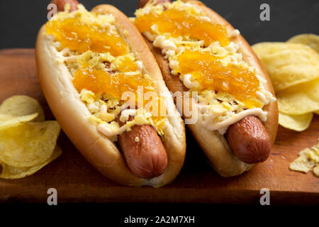 Homemade colombian hot dogs with pineapple sauce, chips and mayo ketchup on a rustic wooden board on a black background, side view. Close-up. - Stock Photo