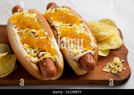 Homemade colombian hot dogs with pineapple sauce, chips and mayo ketchup on a rustic wooden board on a white wooden surface, side view. Closeup. - Stock Photo