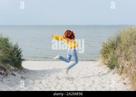 Exuberant agile young woman leaping in the air with outstretched arms on a sandy tropical beach in autumn sunshine - Stock Photo