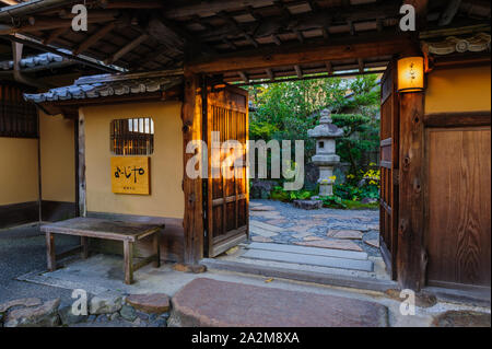 Beautiful oriental entrance to a traditional japanese house in warm evening light, Kyoto Japan - Stock Photo