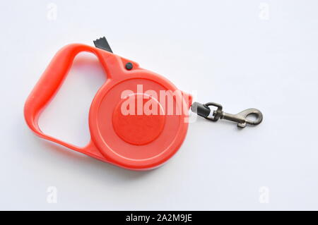 red automatic leash and roll black rope on white background - Stock Photo