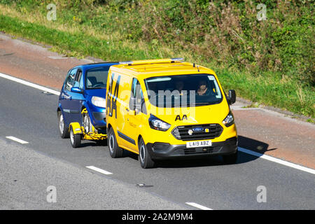 AA Van yellow recovery truck, Ford Transit Custom 340 Base carrying broken down van; Side view of rescue breakdown recovery vehicle transporting small family car along  M6, Lancaster, UK; Vehicular traffic, transport, modern, north-bound on the 3 lane highway. - Stock Photo