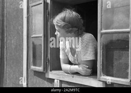 Eine junge Frau schaut aus dem Fenster heraus, Deutschland 1930er Jahre. A young woman looking out of the window, Germany 1930s. - Stock Photo