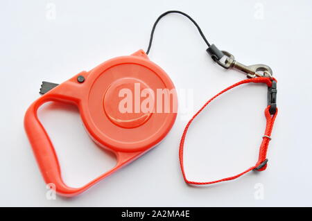 red automatic leash and pink nylon cat collar on white background - Stock Photo