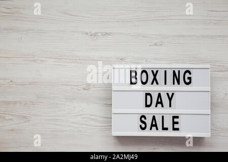 'Boxing day sale' words on a lightbox on a white wooden background, top view. Overhead, from above. Copy space. - Stock Photo